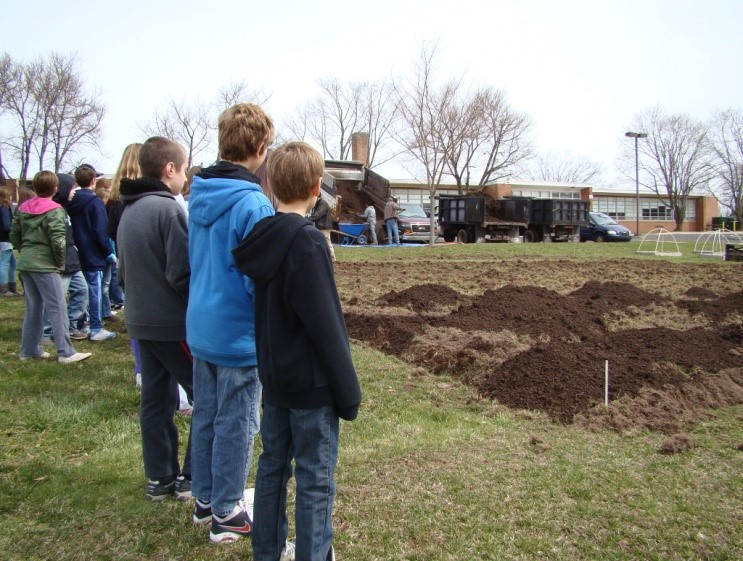 Salford Hills Elementary Students watch as topsoil is mixed in with the freshly tilled ground to provide a welcoming bed for our new 50x50ft. vegetable patch.